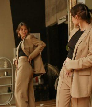 Une jeune femme essaye devant un miroir comment lui va un tailleur pantalon (photo prétexte d'une banque d'image)