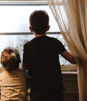 Deux enfants regardent par la fenêtre