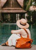 Femme avec un sac 48h à l'épaule, assise devant une piscine