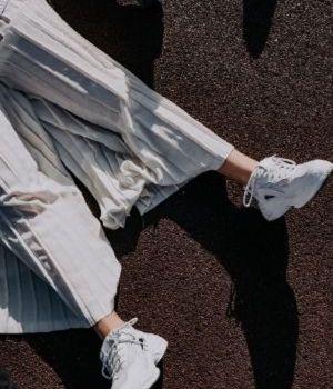 Une personne en jupe blanche plissée et baskets blanches allongée au sol