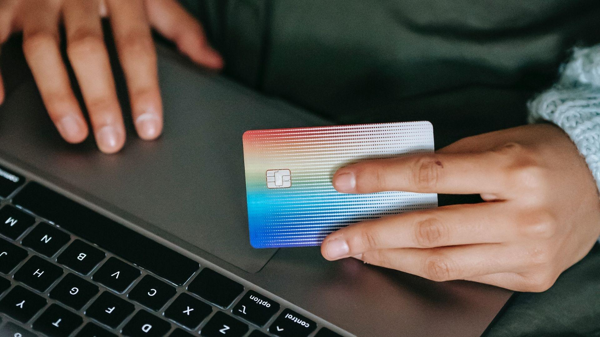 Personne surfant sur internet, une carte de crédit Mastercard à la main